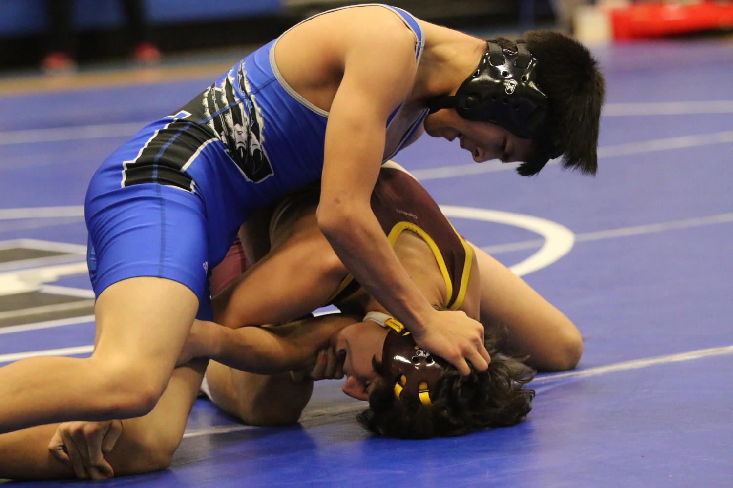 Varsity Wrestler, Joey Arroyo, holds his opponents head in hopes to maintain control.