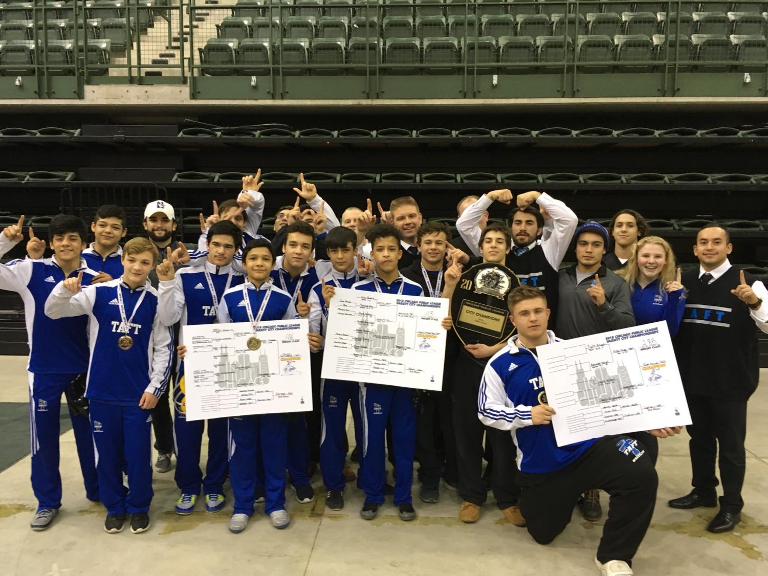 Taft wrestlers and coaches posing with their personal and team awards after Day 2 of the City Championships.