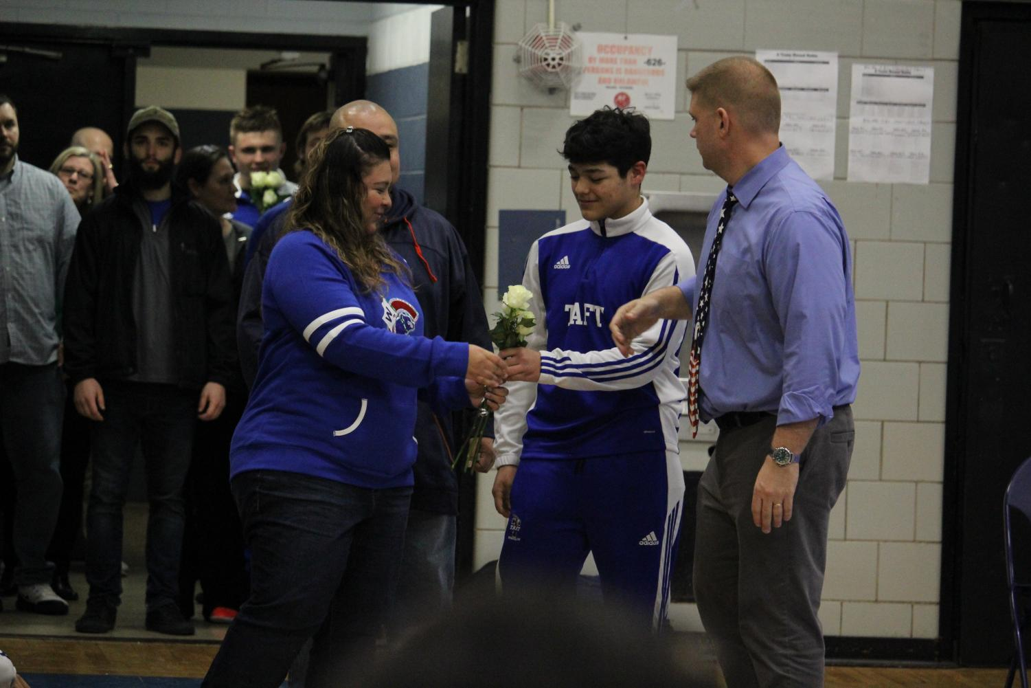 Senior Noe Arroyo handing his mother the roses he received while being congratulated by Coach Brad Engel