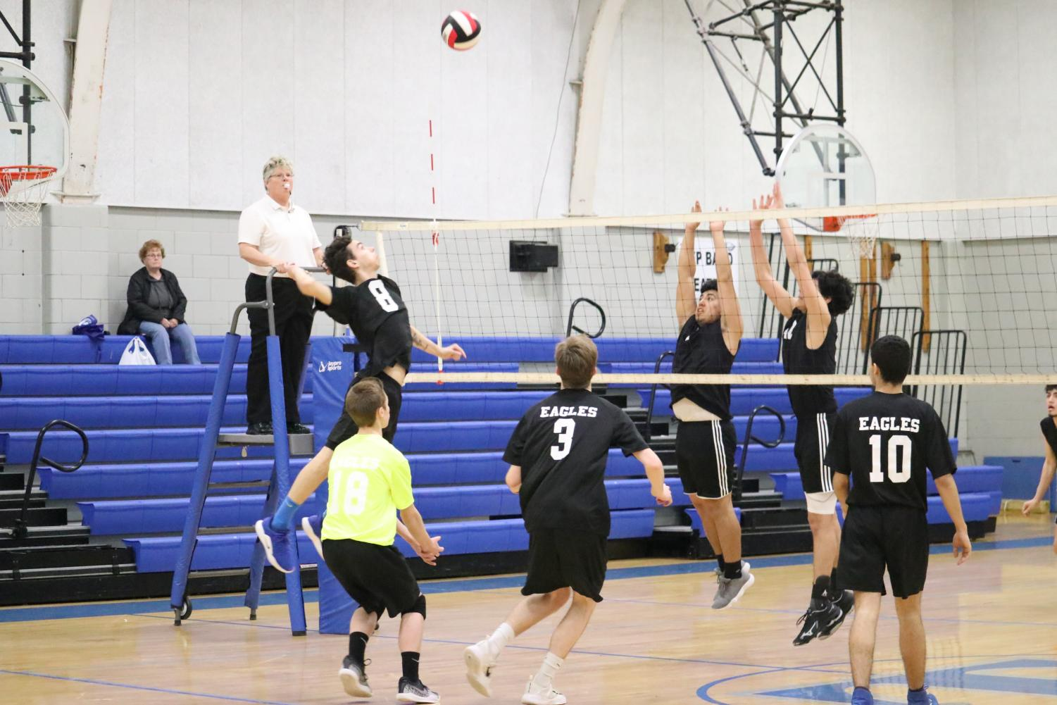 Louie Piatkowski soaring high to throw down a powerful spike against a rival team.