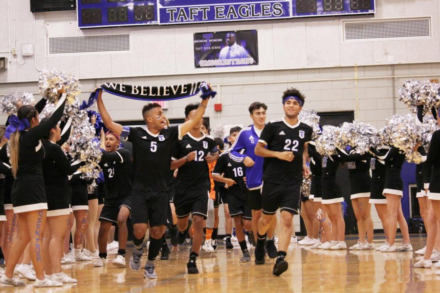 """Taft's soccer team rushes in to a crowd of screaming fans and cheerleaders, holding a banner titled """"We Believe"""".                                                                                  Photographer Carmella Gilio."""
