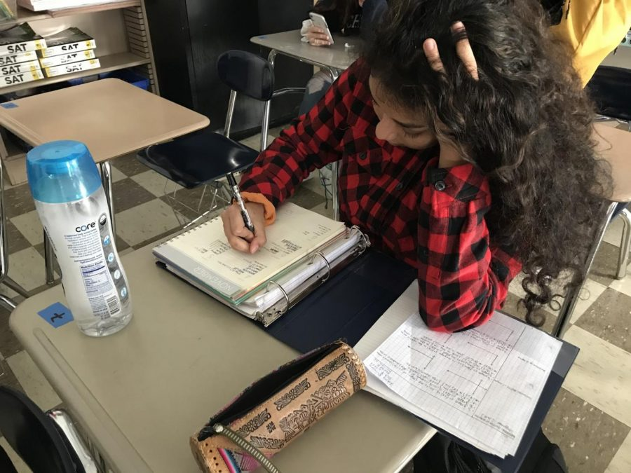 Ashley Briceño in her AVID class, writing down assignments that she will need to catch up on over the weekend.               Photographer Vivian Aviles.