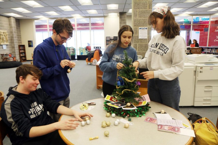 Students in Drama Club decorate their Christmas tree with ornaments that represent their club.  Photographer Yasmine Soria.